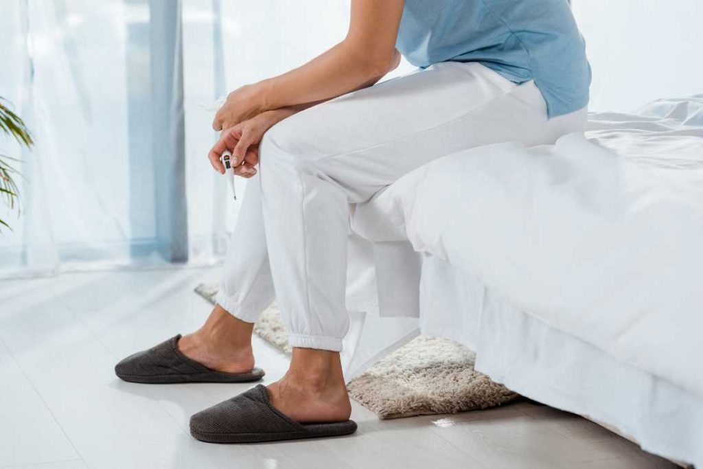 Woman Sitting On Edge Of Bed Wearing Slippers